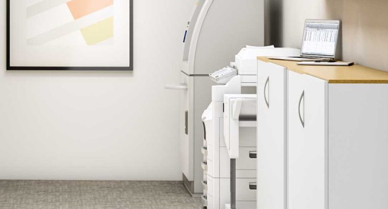 White printer in modern office resource area with grey carpet and framed art on the wall
